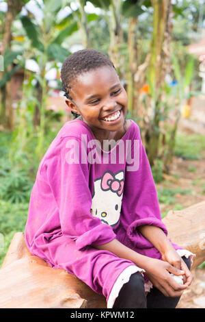 Ein schönes Lachen ugandischen Mädchen sitzen auf einen umgestürzten Baumstamm. - Stockfoto