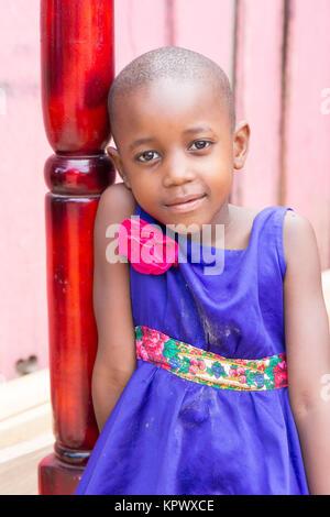 Eine schöne Ugandischen lächelnde Mädchen. Sie ist in einem blauen Kleid mit einem rosa Blume darauf gekleidet. - Stockfoto
