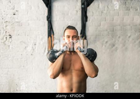 Mann Anheben zwei Kettlebell Workout im Fitnessraum - Stockfoto