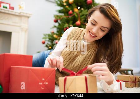 Neugierig Frau Auspacken Weihnachten Geschenkverpackung - Stockfoto