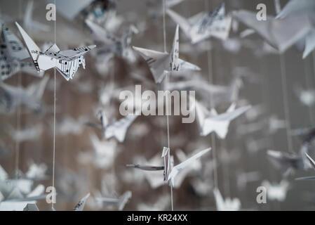 Schwarm von origami Kraniche aus Musik Manuskript Papier - Stockfoto