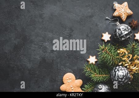 Stilvolle Weihnachten Hintergrund mit Vintage Spielzeug, Tannenbaum und Cookies auf schwarzen Stein Hintergrund. - Stockfoto