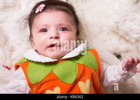 Close-up Portrait von einem schreienden Baby Mädchen mit bunten Pullover liegen auf pelzigen weißen Decke, Ansicht - Stockfoto