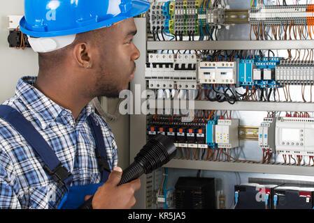 Techniker Analyse Sicherungskasten mit Taschenlampe - Stockfoto