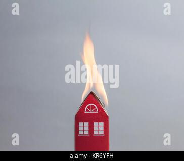 Haus Feuer Konzept. Spielzeug Haus mit Flammen Stockfoto