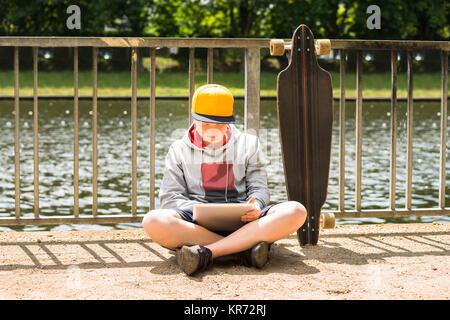 Junge tragen Sie die Kappe mit digitalen Tablet - Stockfoto