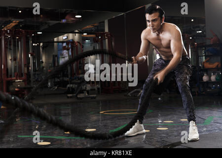 Junge Männer trainieren Sie im Fitnessraum - Stockfoto