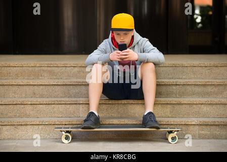 Junger Mann, der Kappe an Handy suchen - Stockfoto