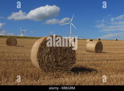 Stoppel mit Heuballen und Windenergieanlagen im Hintergrund gegen den blauen Himmel Weisse Wolken - Stockfoto