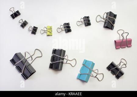 Haufen Metall binder clips für Papier, verschiedene Größen und Farben. In der Zeile festgelegt - Stockfoto