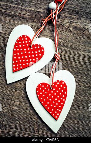 zwei dekorative rote und weiße Herzen auf einem hölzernen Hintergrund. - Stockfoto