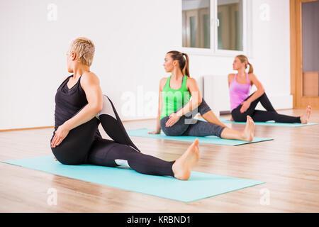 Drei Mädchen üben Yoga, matsyendrasana/Spine-Twisting darstellen - Stockfoto