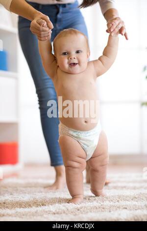 Cute Baby Boy, die ersten Schritte mit Mutter - Stockfoto