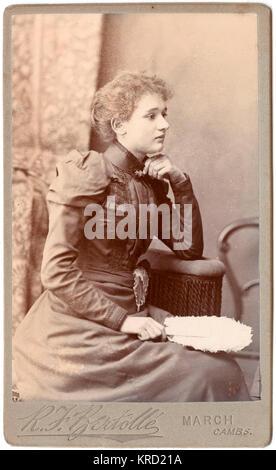 Eine junge Viktorianische Frau posiert im Studio des Fotografen, trug ein elegantes Kleid mit Stehkragen und Stickerei am Oberteil und am Ärmelabschluss. Sie ist im Profil sitzend, mit einer weißen Feder Lüfter in der Hand. Datum: ca. 1890 s Stockfoto