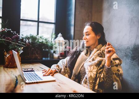 Schöne junge Mädchen nutzt laptop Technik, Typen text am Monitor in einem Café auf der Suche durch das Fenster an - Stockfoto