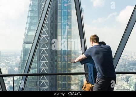 Paar genießen den Blick auf die City von London mit dem Leadenhall Building in der Front. Von der Dachterrasse im - Stockfoto