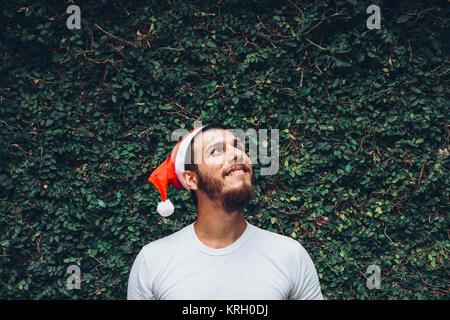 Junge brunette Mann mit einem Weihnachten Kappe, über eine Textur vegetal Hintergrund, suchen und lächelnd - Stockfoto