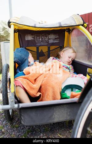 Zwei junge Kinder schlafen in einem Fahrradanhänger - Stockfoto