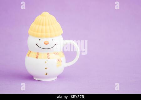 Farbige Porzellanbecher als Schneemann auf lila Hintergrund - Stockfoto