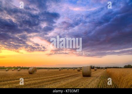 Sonnenuntergang über Feld-Hof mit Heuballen - Stockfoto