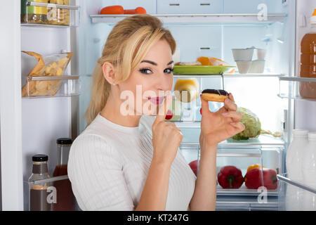 Frau heimlich Essen Donut aus dem Kühlschrank - Stockfoto