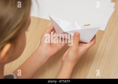 Eine Mädchen schaut auf ein Papierschiff von hand gefertigt - Stockfoto