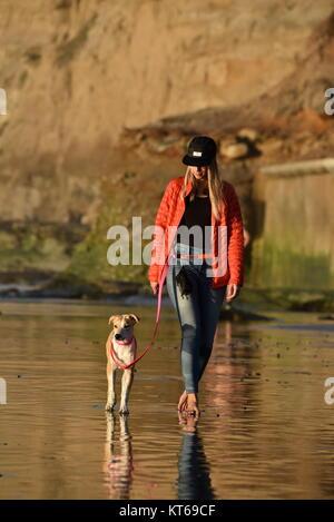 Attraktive Frau in roter Jacke und Jeans walking Hund am Strand bei Sonnenuntergang in La Jolla, San Diego, Kalifornien, - Stockfoto