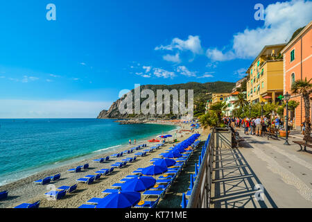 Der breite Sandstrand von Monterosso, Cinque Terre Italien mit Touristen, blaue Schirme und Stühle und das Ligurische - Stockfoto