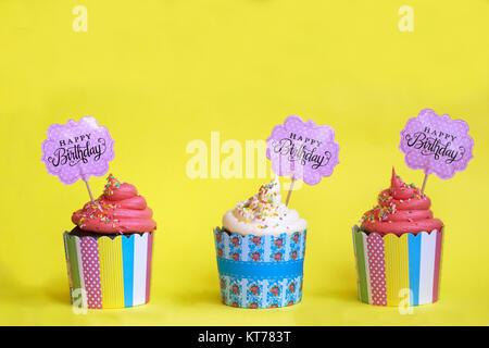 Drei leckere Erdbeere cupcakes in bunten Papier Backformen, mit Happy Birthday Grußkarte, auf gelben Hintergrund. - Stockfoto