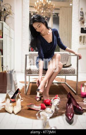 Junge Frau einkaufen in Schuhgeschäft - Stockfoto