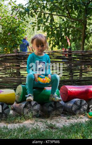 Kleines Mädchen mit einer Spielzeugkamera in den kreativen Prozess - Stockfoto