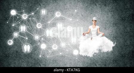 Frau in weißen Kleidern halten die Augen geschlossen und Suchen während der Meditation auf Flying Cloud in der Luft - Stockfoto