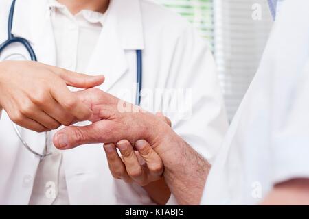 Krankenschwester Kontrolle hand Gelenke des älteren Mannes Stockfoto ...