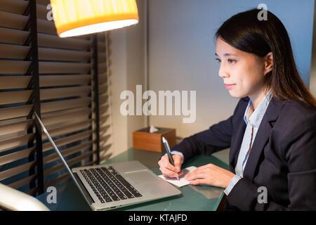Geschäftsfrau schreiben auf die Note mit Laptop