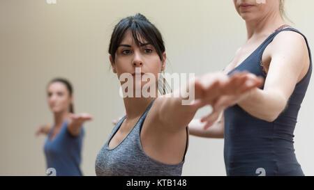 Yoga professioneller Ausbilder helfen, eine Frau, die ihre Arme zu strecken und Balance - Stockfoto