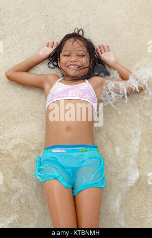 Eine junge philippinische Mädchen ca. 7 Jahre alten erfreut sich die Verlegung in die Brandung am Strand von Pandan - Stockfoto