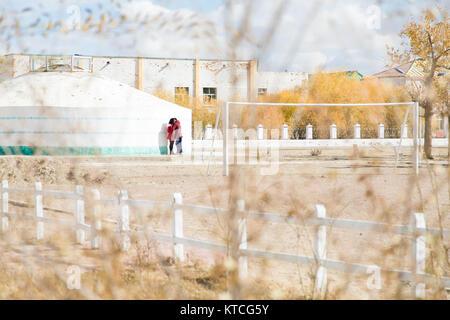 Ein junges Paar in der Mongolei stehlen einen Kuss von Herbstlaub gerahmt