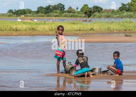 Drei Jungen madagassischen kids Wave, während der Reinigung die Töpfe mit Sand an einem Flussufer. Madagaskar, Afrika. - Stockfoto