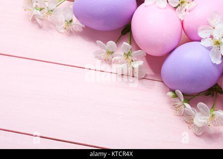 Ostereier und weiße Blumen auf rosa Holztisch. - Stockfoto