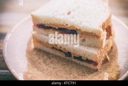 Peanut Butter und Marmelade Sandwich auf Weißbrot, halbiert und gestapelt. Auf kleinen vintage Platte gezeigt - Stockfoto