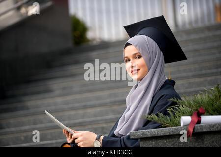 Hübsche junge weibliche Absolventin hijab tragen - Stockfoto