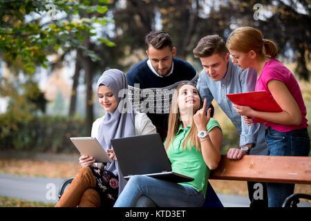 Gruppe von Jugendlichen mit Notebook und Tablet-PC auf einer Parkbank, Spass haben, Reden, heraus hängen - Stockfoto