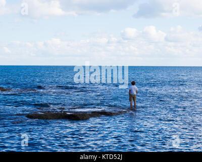 Mann verkleidet in T-Shirt und Shorts mit einer Hand in der Tasche stand auf Halb unter Wasser Felsen Angeln im - Stockfoto