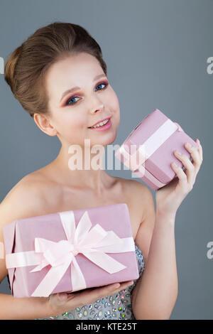 Schönen, gesunden Modell Frau mit Geschenk Box auf grauem Hintergrund - Stockfoto