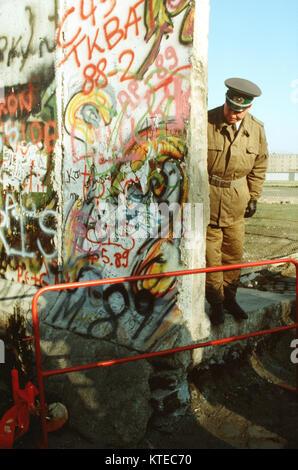 Ein Ostdeutscher Polizist schaut auf einen kleinen Weihnachtsbaum schmücken die Westdeutsche Seite der Berliner - Stockfoto