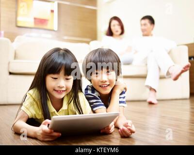 Zwei asiatische Kinder liegen auf dem Boden spielen video game mit digitalen tablet, während die Eltern im Hintergrund. - Stockfoto