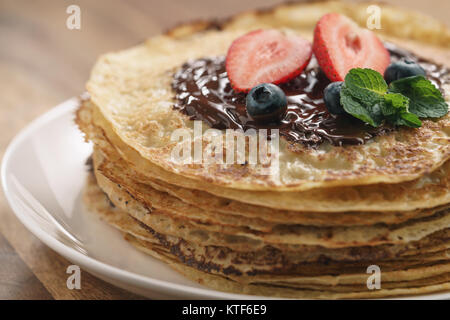 Stapel Pfannkuchen mit Beeren und dunkler Schokolade auf der Oberseite gegossen - Stockfoto