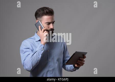 Ernsthafte selbstbewussten jungen Geschäftsmann am Telefon zu sprechen und auf der Suche nach Tablet Computer über - Stockfoto
