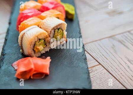Detailansicht der bunten japanischen Sushi Rollen serviert mit Ingwer auf schwarz Tablett im Restaurant - Stockfoto