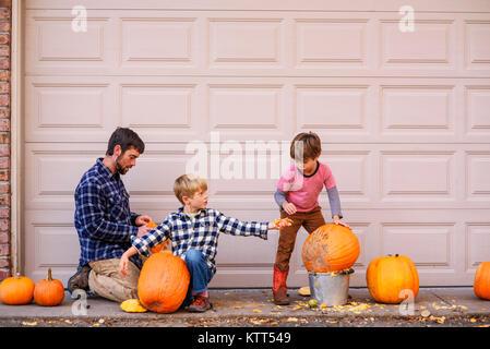 Zwei Jungs und ihr Vater schnitzen Halloween Kürbisse - Stockfoto